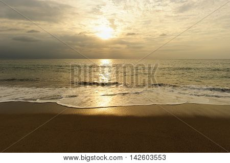 Golden ocean sunset is a beach scenic with a soft bright ethereal light relecting off a wave at it gently moves to shore.