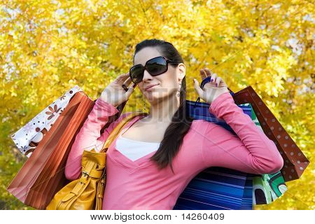 Modern girl with shopping bags and phone