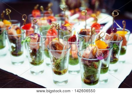 Various snacks in shot glasses on table