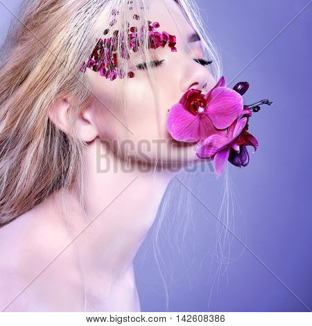Beautiful girl, isolated on a light - grey background with varicoloured flowers on fase, emotions, cosmetics