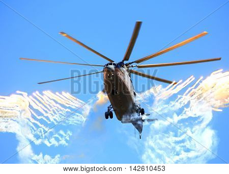 Modern russian military helicopter shooting back a false heat targets
