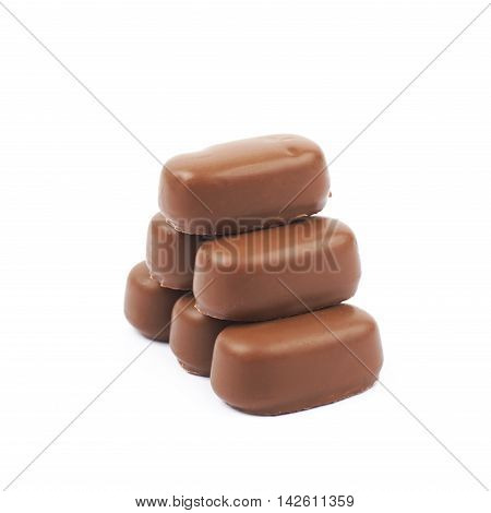 Pile of chocolate coated toffee candies isolated over the white background