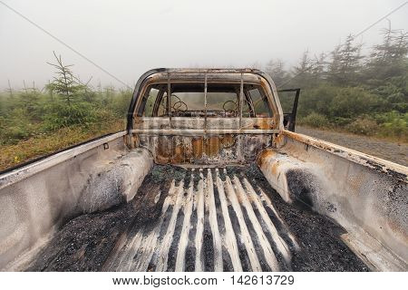The Back Of A Burnt Out Pick Up Truck Looking Forward