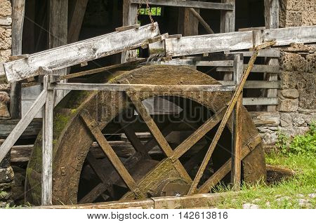 Old retro wooden mill wheel powered by water closeup
