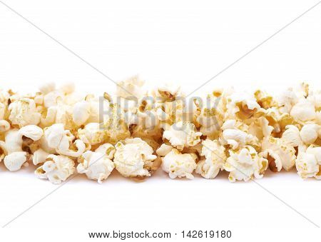 Line pile of the popcorn flakes isolated over the white background, close-up crop composition