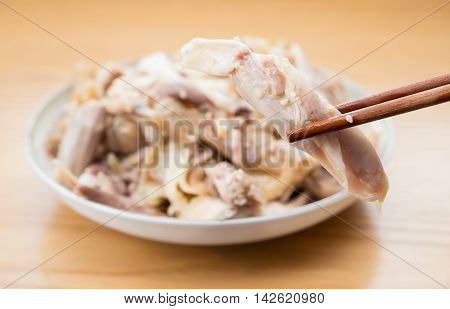 chopsticks picking up piece of shredded boiled chicken from a dish
