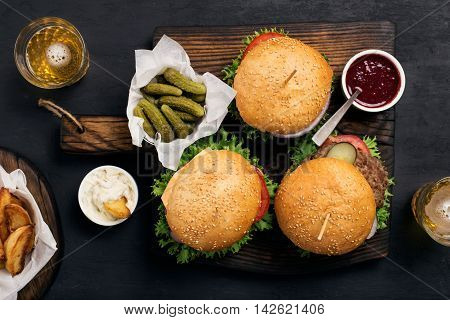 Three different burger on massive wooden board with pickles ketchup mayonnaise fries and light beer top view