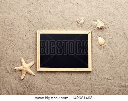 Blank blackboard on sand with shells and starfish top view