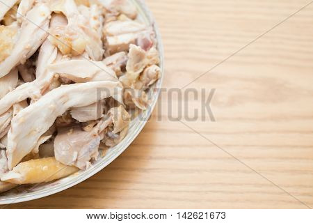 dish of shredded boiled chicken on wood table with copy space
