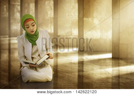Young Woman Asian Muslim Wearing Hijab, Reading The Koran
