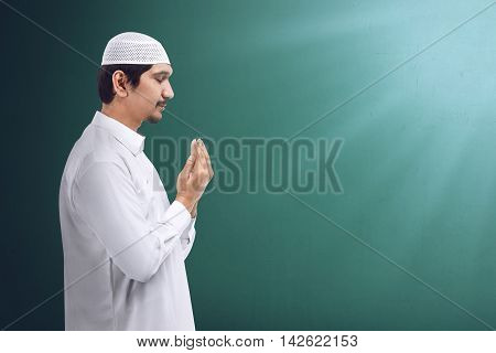 Young asian muslim man praying to god muslim dress and wear caps