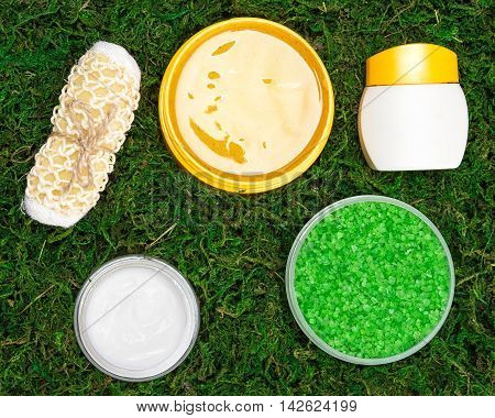Spa and pampering products: body scrubber, open jars filled with coarse sea salt, natural body scrub and skin care cream on green moss. Safe organic cosmetics
