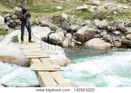 Aadventurous Photographer Aleem Zahid Khan on dangerous flooded river swat valley. standing on a bridge and capturing the moment with his camera on tripod.