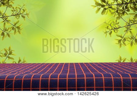 Empty table and tablecloth with blur green leaves bokeh background for product display montage