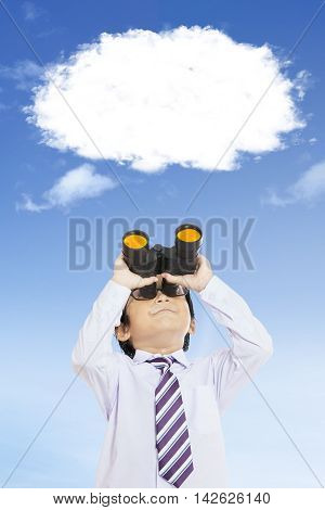 Male elementary school student looking at the empty speech bubble with a binoculars shot outdoors