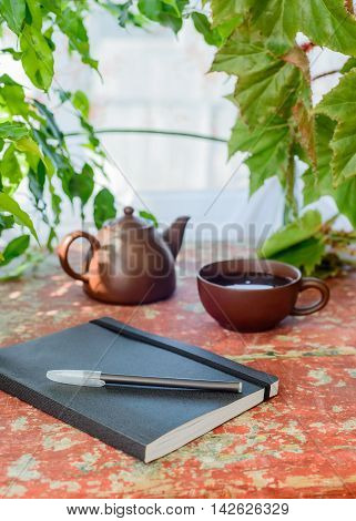 pen, notebook and tea on a wooden table