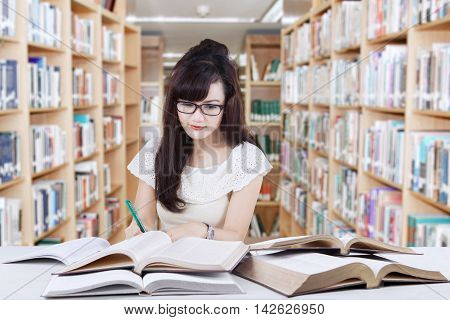 Photo of a smart female student sitting in the library while doing assignments and reading book to the source of her task