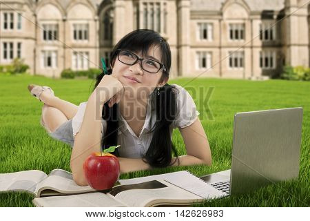 Photo of a clever high school student smiling happy while daydreaming and studying at the park