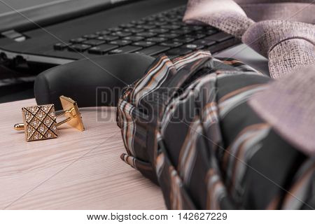 Fashion and business notebook and cufflinks on a wooden table as background