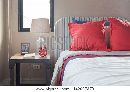 Red And Blue Pillows On The Cozy Bed With Striped Headboard