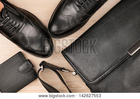 Classic black shoes briefcase and purse on the wooden floor can be used as background