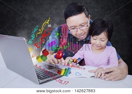 Photo of young father helping his daughter to study with formula of science math and mathematics on the laptop