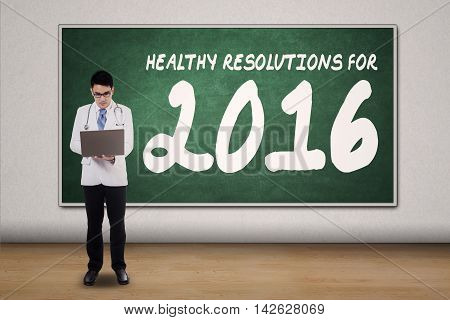 Full length of a male general doctor using laptop computer with healthy resolutions for 2016 on chalkboard
