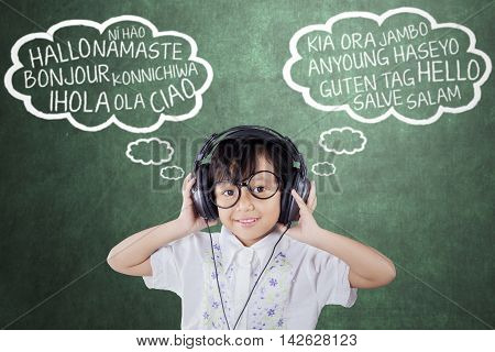 Little girl using headphones to listen and learn foreign languages in the classroom