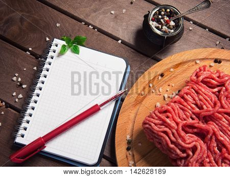 Raw Minced Meat And Blank Notepad On Rustic Wooden Background
