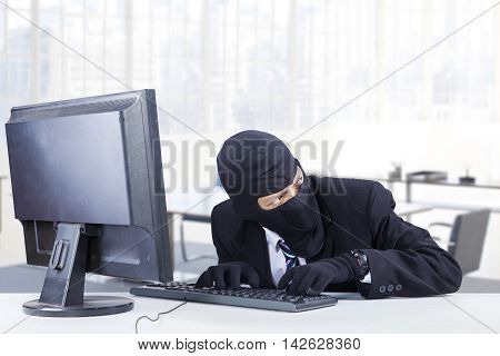 Male hacker wearing mask and steal data on the computer in the office while looking at around him