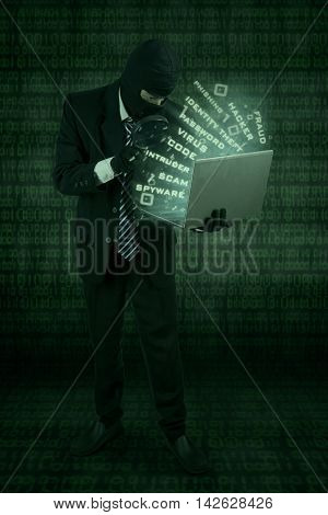 Male hacker using magnifier and wearing mask to steal information on the laptop