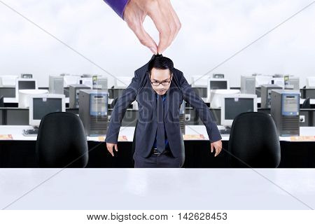 Picture of hand holding a businessman in the office and put him on the office chair