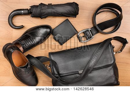 Classic black shoes briefcase belt and umbrella on the wooden floor can be used as background