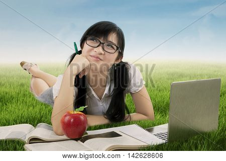 Photo of happy female high school student lying on the meadow while daydreaming and studying with book