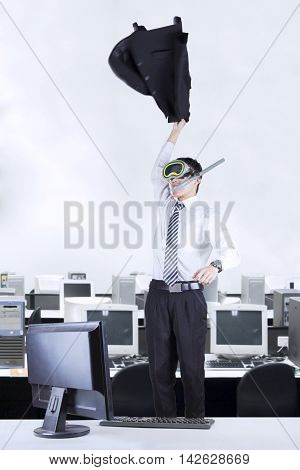 Cheerful businessman expressing his success while standing in the office and wearing goggles with computer on desk