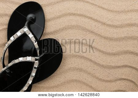 Beach black flip flops encrusted with rhinestones standing on the sand with space for your text
