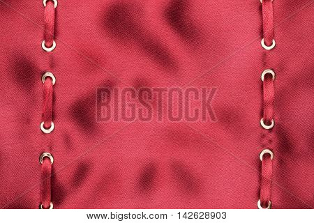 Red satin ribbon inserted in the gold rings on red silk with space for your text