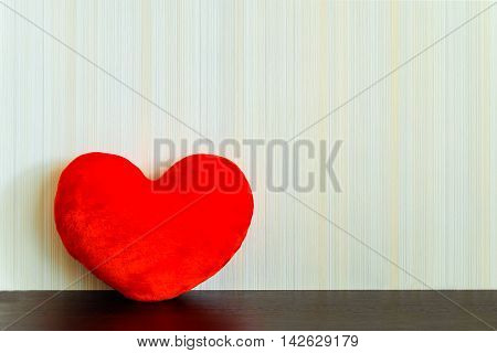 Red fabric heart on a wooden surface wenge color on the background wall with texture in a vertical strip. Love concept. Background with copy space.