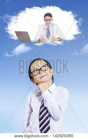 Male elementary school student thinking dream job while looking up at speech bubble shot outdoors