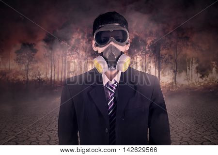 Portrait of a businessman wearing gas mask with forest fire background