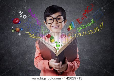 Cute female elementary school student holding a book with formula of science math and physics. Shot in the classroom