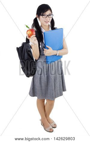 Portrait of a beautiful high school student standing in the studio while holding apple fruit and carrying backpack