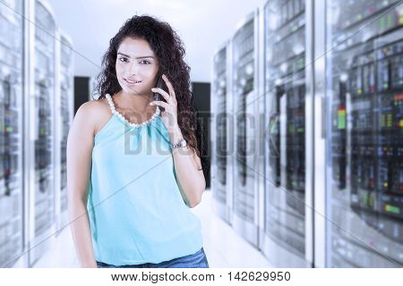 Pretty indian woman standing in the server room while speaking on her mobile phone