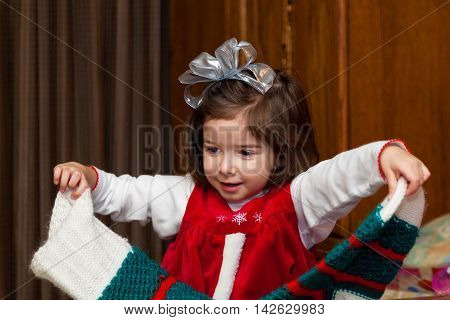 A little girl hold her giant empty stocking on Christmas morning after she has emptied it. She is happy.