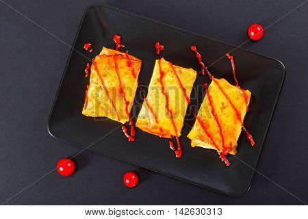 rolls of pancake or crepes stuffed with minced meat poured with ketchup on dish poured with ketchup cherry tomatoes on black background view from above close-up