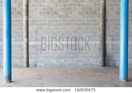 interior background exposed concrete block wall and dirty floor blue column
