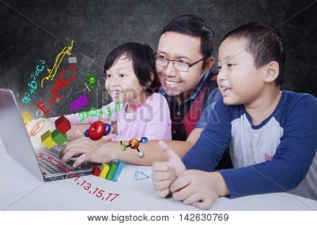 Male teacher and his students using laptop computer in the classroom with formula of science math and physics