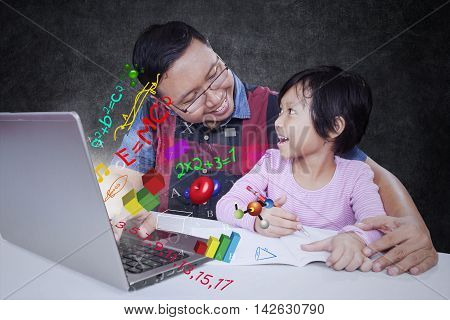 Male teacher talking with his elementary school student while using laptop computer with formula of science math and physics
