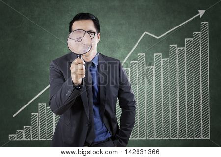 Young businessman looking through a magnifying glass with financial graph background