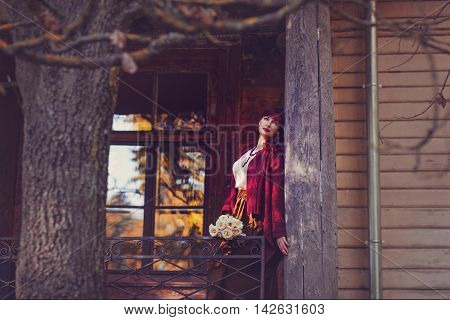 Beautiful young woman with flowers in long skirt and wool red scarf standing on old house balcony. Early fall. Outside shot. Ambient light.